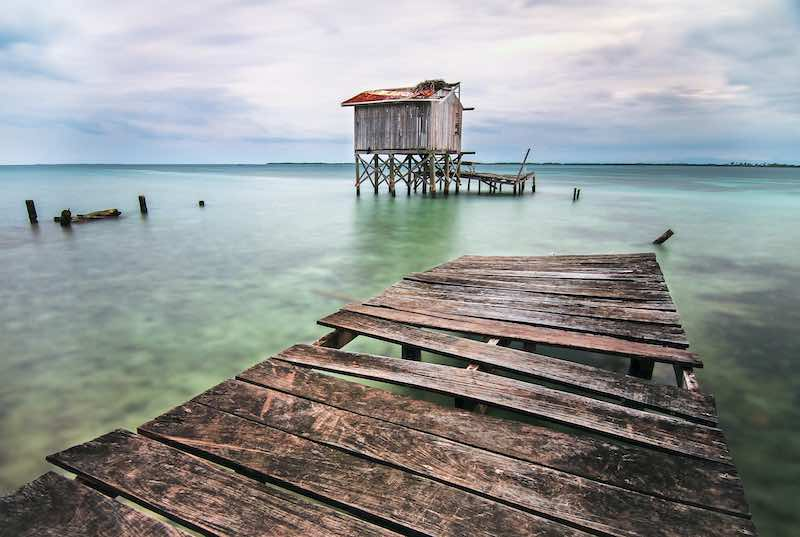 Old dock in the Caribbean Sea. Belize Tours Packages. Central America Travel Agency. Guatemala and Belize Tour