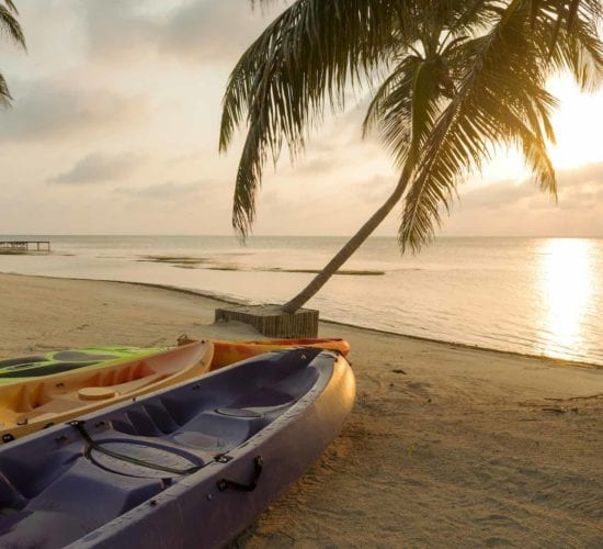 Kayaks sitting on the beach at dawn with a beautiful sunrise in a small island of Belize.