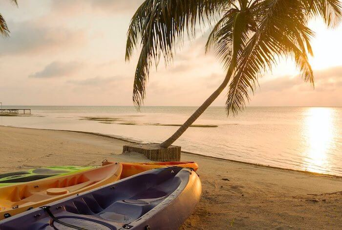 Kayaks in a tranquile beach of Belize during sunset after a kayaking excursion.
